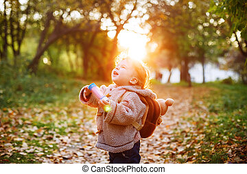 Happy kid boy in autumn park walking outdoors, sunshine...