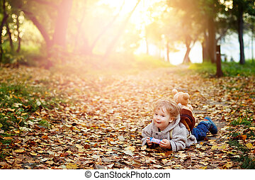 Happy kid boy in autumn park lying in fall yellow leaves and...