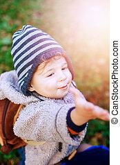 Happy kid boy in park walking outdoors, sunshine around