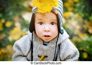 Close up of cute curious little boy with yellow leaf in a...