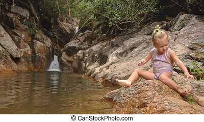 Little Blond Girl Sits Cleans Foot on Stone by Waterfall -...