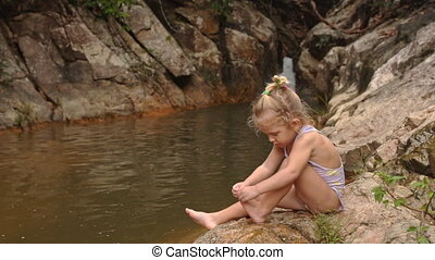 Little Blond Girl Sits Cleans Foot on Stone by Waterfall