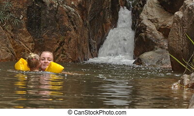 Little Blond Girl in Arm-hands Swims at Waterfall