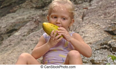Closeup Little Blond Girl Sits Eats Mango on Stone - closeup...