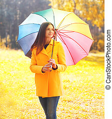 Portrait beautiful woman with colorful umbrella in warm...