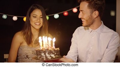 Pretty young woman celebrating her birthday blowing out the...