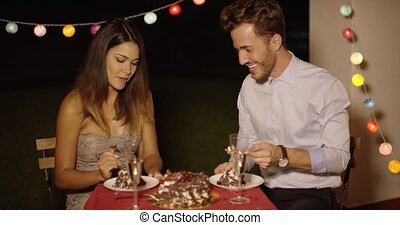 Loving young man feeding his girlfriend cake