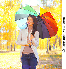 Happy smiling woman with colorful umbrella in warm sunny...