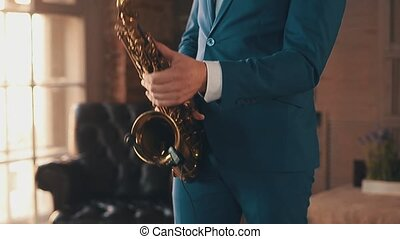Saxophonist in blue suit play jazz on golden saxophone at stage. Elegance.
