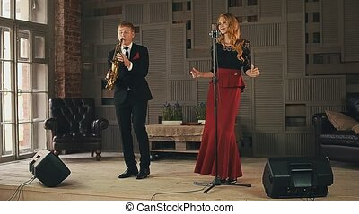 Jazz vocalist click fingers on stage, saxophonist in black...