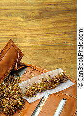 Rolling tobacco pouch - Close up of tobacco and rolling...