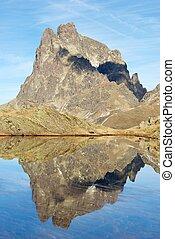 Pyrenees - Midi Dossau Peak reflected in a lake. Ossau...