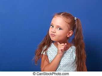Serious makeup thinking kid girl with long hair looking on...