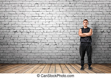 Muscled young man standing with his arms folded on the...