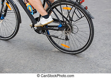 cyclist goes by bicycle down street detail