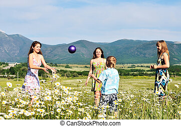 children playing a ball in fiels - boy and teen girls...