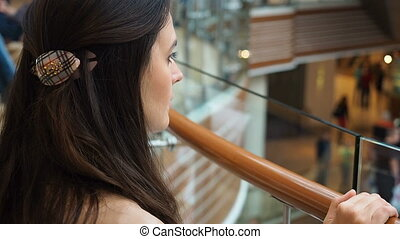 Young girl looking from the top floor on people in trade...