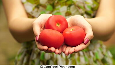 footage Woman holding a tomato close up.