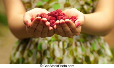 footage Woman holding a raspberry close up.