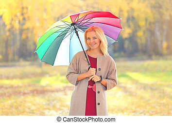 beautiful smiling woman with colorful umbrella in warm sunny...