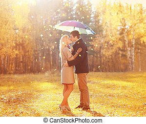 Happy romantic kissing couple in love with colorful umbrella...
