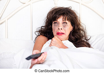 Woman Watching Sad Movie on Television - Mature woman in bed...