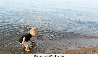 gay boy kid blonde throws a large stone into the water in...