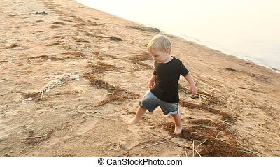 gay boy kid blonde running on the beach in the summer in a...
