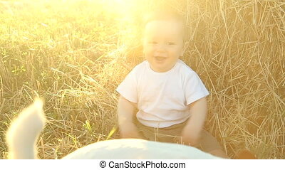 kid in the white shirt plays with a dog in a haystack in a...