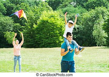 Family Flying Kite In The Park