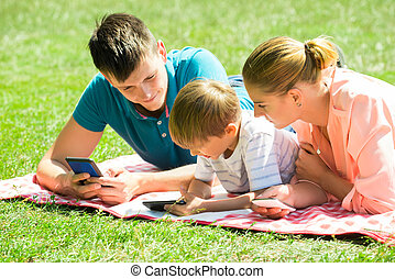 Family Laying Down In The Park With Their Smart Phones -...