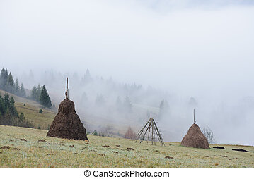 Autumn landscape with haystacks and fog in the mountains -...