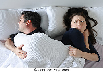 Man hogging the blanket from woman in bed - Man age 35 -4 5...
