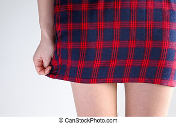 Sexy schoolgirl holds down her short skirt. Women sexuality...