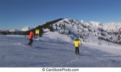 Skiers accompanied by cameraman - two skiers being...