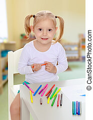 The girl draws with markers