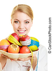 Woman holding fruits dietitian recommending healthy food -...