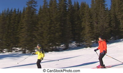 Skiing - Two skiers heading down a moderate hill being...