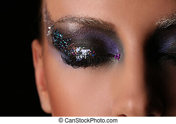 Woman's smokey eye with colorful crystals. Close up. Black background