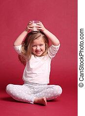 Sitting child girl in sleepwear drinking milk. Red background