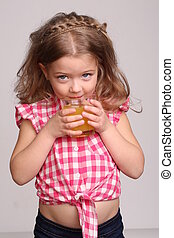 Portrait of a girl drinking orange juice. Close up. Gray background