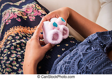 Pregnant Woman With Newborn baby shoes