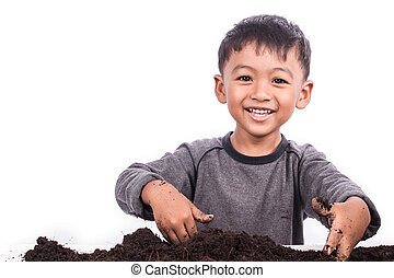 little boy preparing the soil for planting