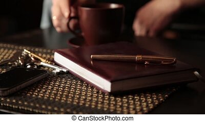 closeup diary, man takes notes and drinking coffee.
