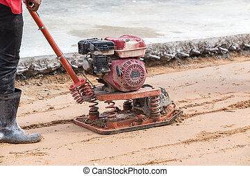 Worker with red soil compactors in construction site -...