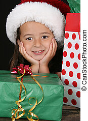 Christmas gifts - Cute brunette girl sitting amongst...