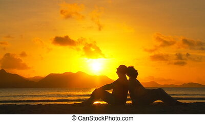 elderly couple enjoying sunset - senior couple sitting back...