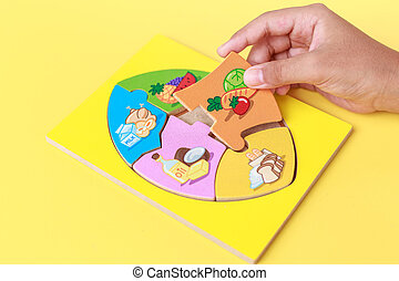 Hand of kid holding wooden jigsaw of the 5 food Groups Child...