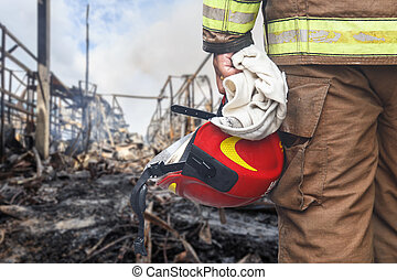 Firefighter holding red safety helmet isolated on white -...
