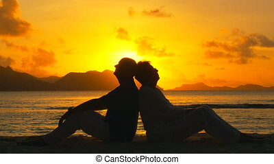 romance at sunset - elderly couple sitting back to back on...